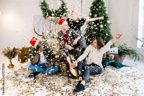 Staande foto Schilderingen Two beautiful young girls and two boys having fun at New Year's party, wearing santa hats, sitting on the floor in front of the Christmas tree and playing with confetti. Christmas concept