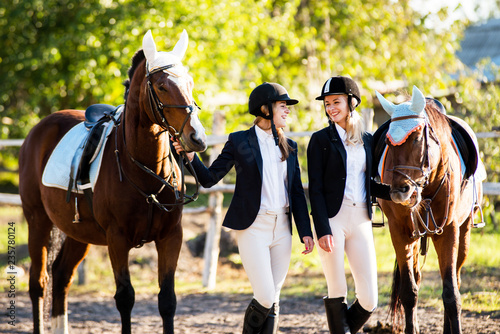Two girls rider stands near a horses. Horse theme