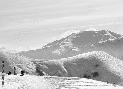 Skiers and snowboarders on snowy road before downhill on off-piste slope