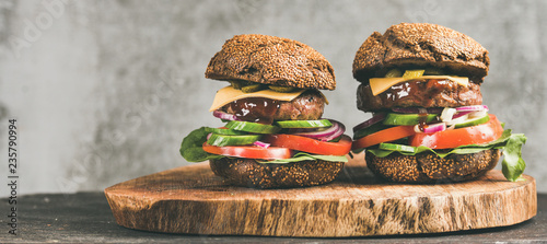 Fotografia Beef meat cheeseburgers with barbeque sauce on rustic wooden board, grey concrete wall at background, copy space, wide composition