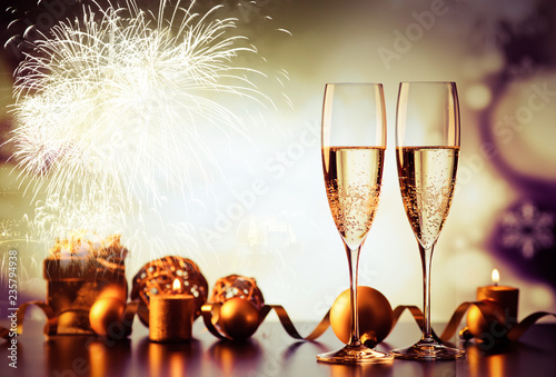 Fotografía  two champagne glasses against holiday lights and fireworks - new year celebratio