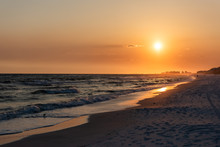 Orange Yellow Sunset In Santa Rosa Beach, Florida With Pensacola Coastline Coast Cityscape Skyline In Panhandle With Ocean Gulf Mexico Waves, Silhouette Of Buildings