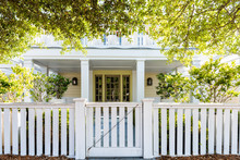 White Beach Wooden Wood Architecture Of House, Door Gate To Front Porch Yard With Green Landscaping Trees, Vacation Cottage Home, Fence