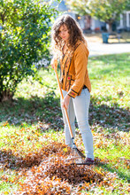 Young Woman, Female Person, Adult Homeowner In Garden Front Yard, Backyard, Working, Raking Collecting Dry Autumn Foliage Oak Leaves Standing With Rake In Fall Winter, Sunny Sunlight, Doing Work