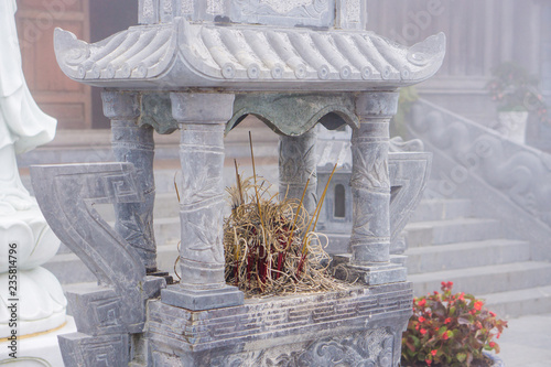 Foto  Incense sticks are smoking near buddhism temple in Fansipan peak, north of Vietn