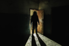 Creepy Silhouette Of Unknown Man With Knife In Dark Abandoned Building. Horror About Maniac Concept