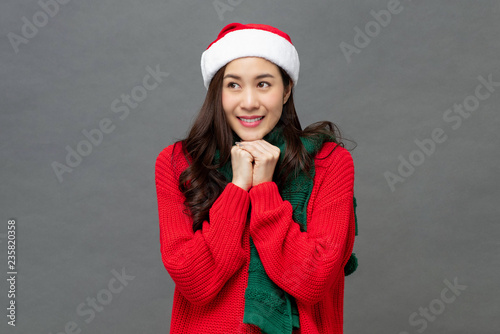 Beautiful asian woman in christmas themed clothes doing an anticipating gesture Canvas Print