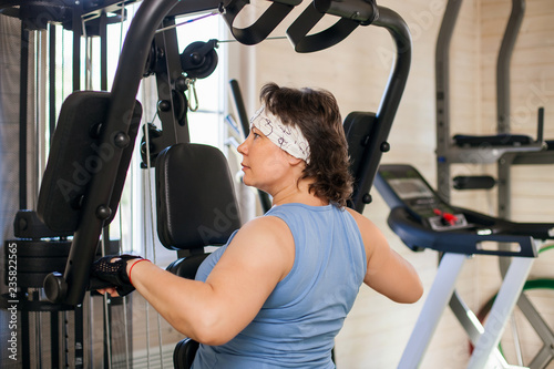 Overweight woman working out on training apparatus home exercise
