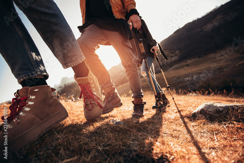 Obraz Hiking man and woman with trekking boots on the trail - fototapety do salonu
