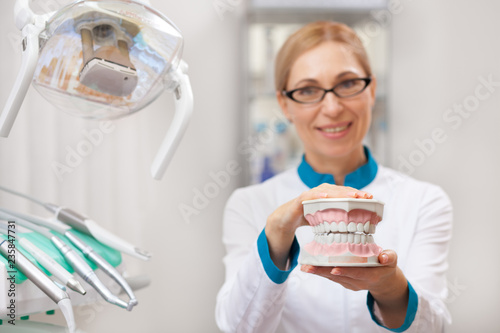 Selective focus on a dental mold in the hands of a mature female