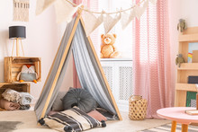 Pillows In Patterned Tent In Kid's Room Interior With Lamp On Wooden Boxes And Toys. Real Photo