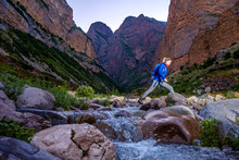 Girl With A Backpack Crosses The River In The Mountains.