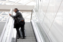 Young African American Travel Man On Escalator With Bags And Mobile Phone