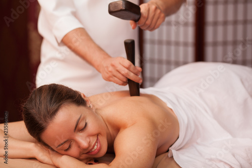 Fototapeta Gorgeous woman smiling with her eyes closed enjoying traditional thai hammer massage at spa center. Beautiful happy woman receiving tok sen massage by professional masseur. Travel, health concapt obraz