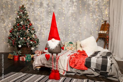 Fotografie, Obraz  Christmas gnome near the Christmas tree at home
