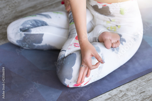 Close-up and details of the yoga hands and legs on lotus pose of a young woman, practicing yoga on blue fitness mat