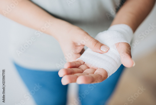 Fotografie, Obraz Woman with gauze bandage wrapped around her hand