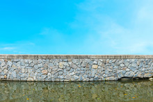 Old Stone Wall With Water And Blue Sky.