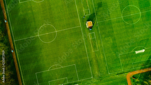 Obraz Aerial image over artificial grass football pitches. Long shadows thrown by a low sun. - fototapety do salonu