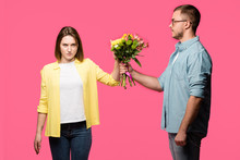 Young Man Presenting Bouquet Of Flowers To Angry Woman Isolated On Pink