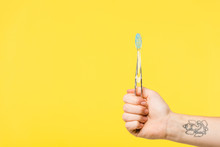 Cropped Shot Of Person Holding Toothbrush Isolated On Yellow