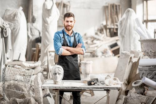 Carta da parati Portrait of a handsome sculptor in blue t-shirt and apron working with stone scu