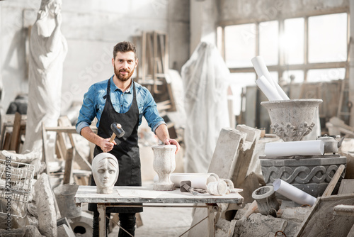 Fotografia Portrait of a handsome sculptor in blue t-shirt and apron working with stone scu