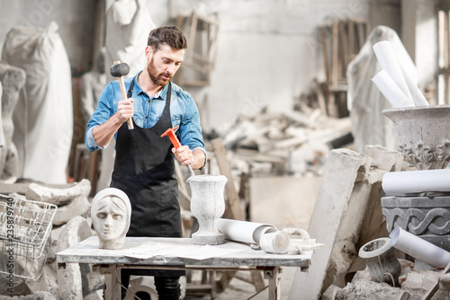 Fotografiet Portrait of a handsome sculptor in blue t-shirt and apron working with stone scu
