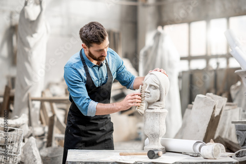 Handsome sculptor brushing stone head sculpture on the table in the atmospheric Fototapeta