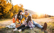 canvas print picture - A young family with two small children having picnic in autumn nature at sunset.