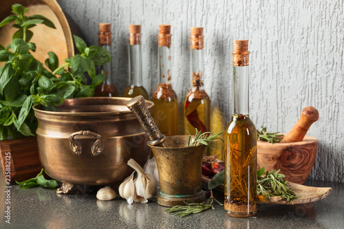 Vintage kitchen utensils with bottles of olive oil.
