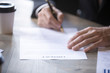 Man in suit fills name form and signs contract with a business partner, employment or insurance contract. Client signs the contract. Recruitment, hiring process human resources, close up view