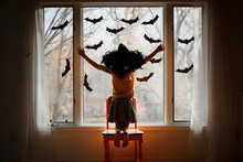 Girl Wearing A Witches Hat Kneeling On A Chair By A Window Decorated With Bats, United States