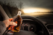 Drink and drive. Driver holding alcohol and driving wheel. Don't Drink for Drive