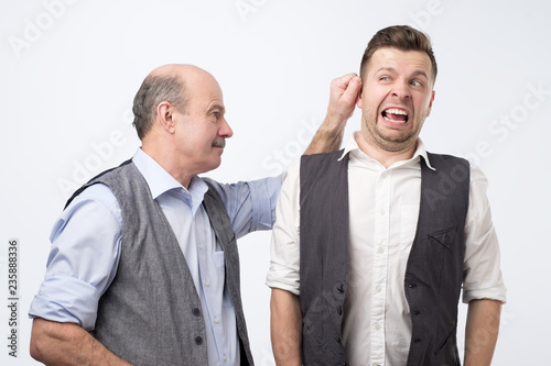 Photo  Senior boss pulling young man ear, punishing for mistake at work.