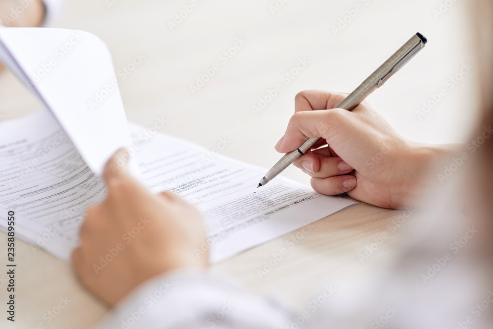 Fototapeta Crop shot of person with pen signing contract at desk in daylight