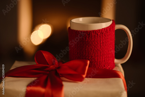 knitted mug and present with bow on blurred background