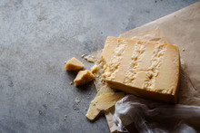 A Block Of Parmesan Cheese On Parchment Paper