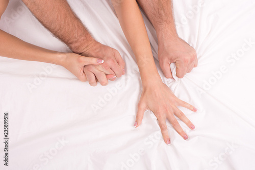 Photographie  couple making love in bed on white crumpled sheet, focus on hands