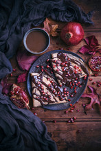Overhead View Of Crepes With Melted Dark Chocolate And Pomegranate Seeds