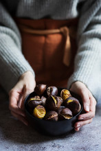 Midsection Of Woman Holding Bowl Of Roasted Chestnuts