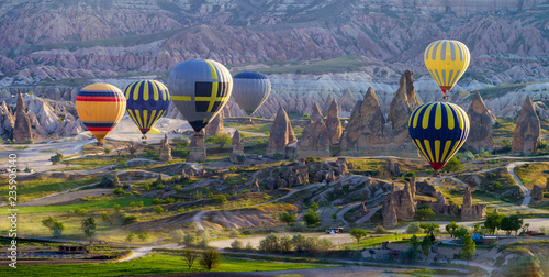 Multicoloured hot air balloons at sunrise flying over Cappadocia, Goreme, Turkey.