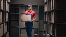 Handsome Warehouse Worker Walks In Storeroom With A Cardboard Box.