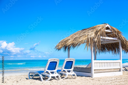 A sun loungers near bed on the sandy beach by the sea and sky. Vacation background. Idyllic beach landscape.