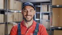 Portrait Of Smiling Uniformed Worker. In The Background, Room With Shelves Full Of Cardboard Box Packages Ready For Shipping.