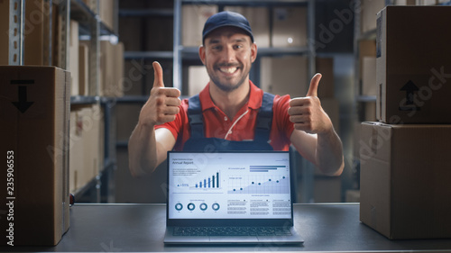 Fotografia  Happy Worker Shows Thumbs Up and Laptop Screen with Infographics Displaying Graph and Statistics with Annual Results Growth