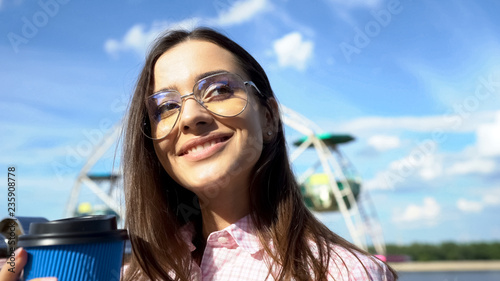 Fotografie, Obraz  Woman greeting guests with cup of beverage, celebrating party on river boat