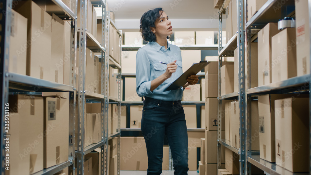 Fototapeta Female Inventory Manager Checks Stock, Writing in the Clipboard. Beautiful Woman Working in a Warehouse Storeroom with Rows of Shelves Full Of Cardboard Boxes, Parcels, Packages Ready for Shipment.