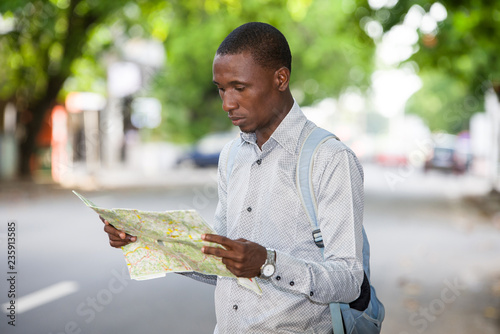 Photographie  Portrait of a young tourist man looking for his landmarks with a map in town