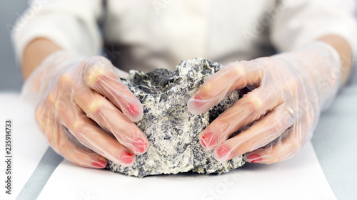 Photo Female hands hold the dangerous mineral asbestos